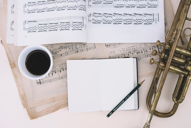 Notebook en koffie in de buurt van bladmuziek en trompet