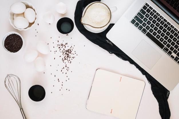 Notebook en laptop in de buurt van ingrediënten en klop
