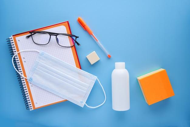 Notebook en pen met een masker op een blauwe achtergrond. terug naar schoolconcept en bescherming tegen covid.