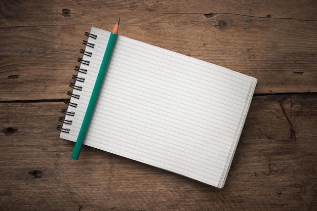 Notebook en potlood op een houten achtergrond