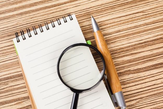 Notebook en vergrootglas. onderzoek idee