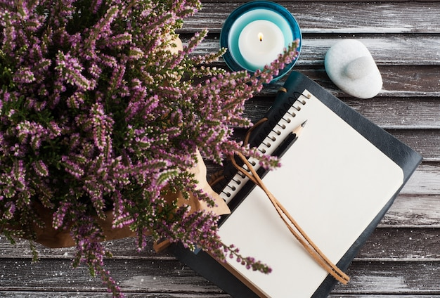 Notebook, heide bloemen en kaars