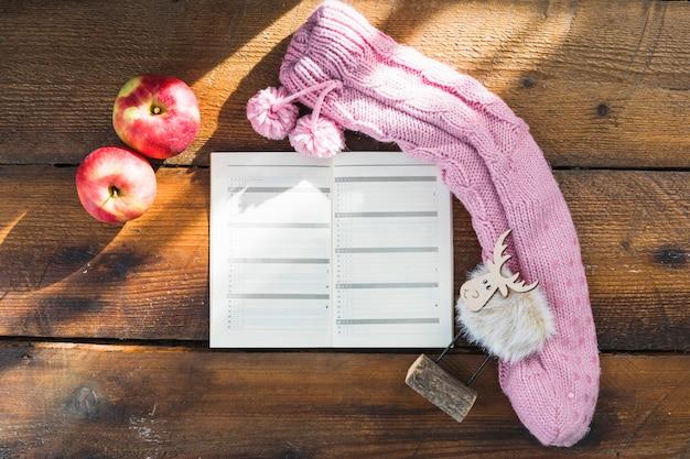Notebook in de buurt van gebreide sok en appels