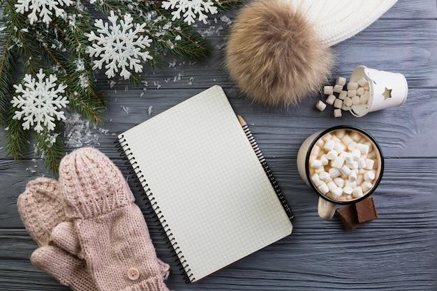 Notebook in de buurt van gebreide wanten, hoed, beker met marshmallows en fir branch