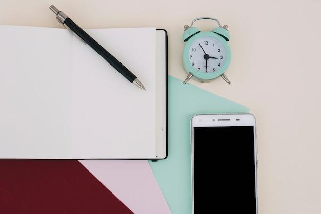Notebook in de buurt van wekker en smartphone