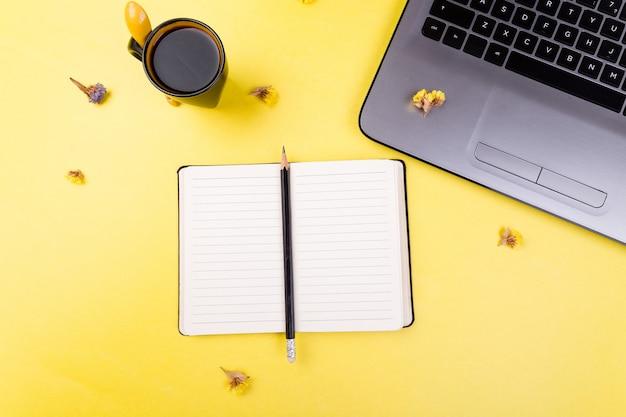 Notebook, koffie en bloemen voor vrouwelijke thuis of op kantoor werkplek,