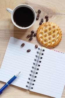 Notebook, koffie en gebak met appelvulling op oude houten