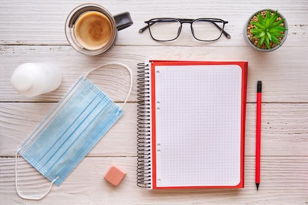 Notebook, koffie en masker op een witte houten tafel. ontwerpconcept, creativiteit en inspiratie. covid-bescherming.