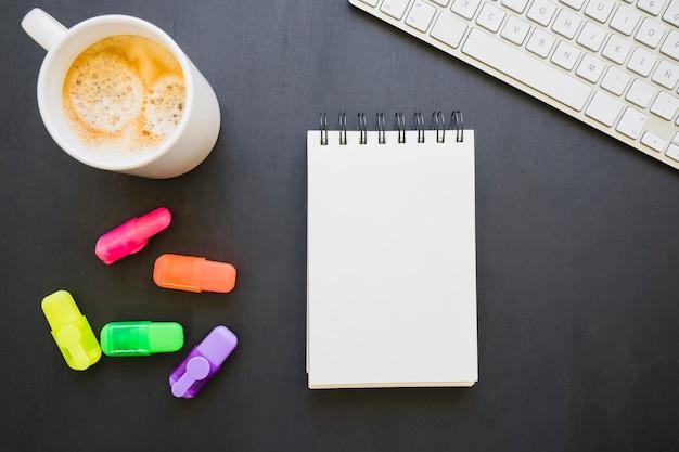 Notebook, koffiemok, markers en toetsenbord