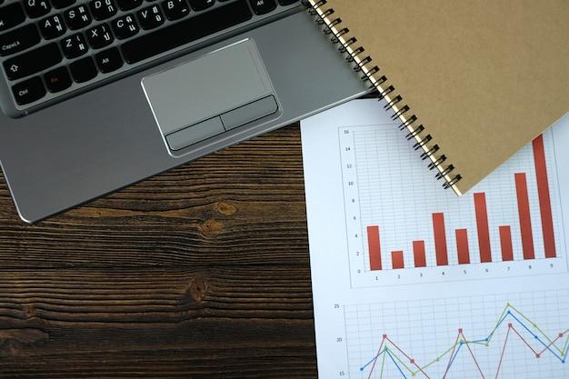 Notebook laptop en financiële grafiek op wit papier