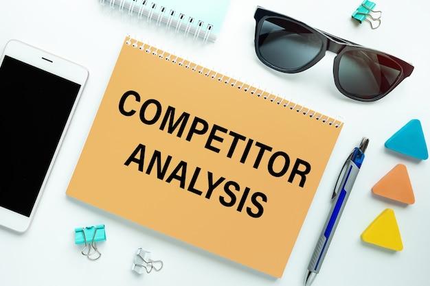 Notebook met tekst competitor analysis omgeven door kantoorbenodigdheden.