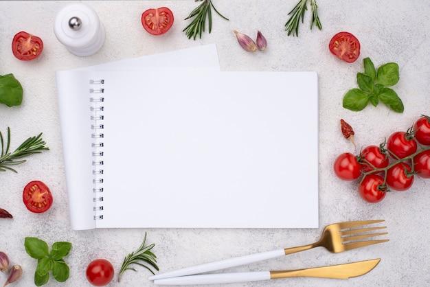 Notebook met tomaten naast