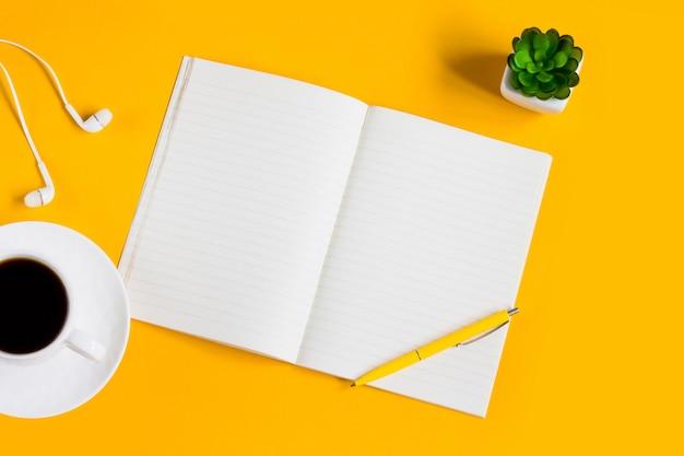 Notebook, mobiele telefoon, planten, pen, koptelefoon op een gele achtergrond met kopie ruimte bovenaanzicht