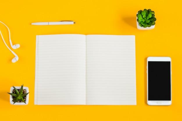 Notebook, mobiele telefoon, planten, pen, koptelefoon op een gele achtergrond met kopie ruimte plat lag.