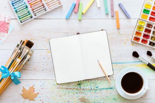 Notebook mock up met art supplies op witte houten tafel, bovenaanzicht, kopie ruimte