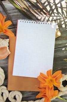 Notebook mock-up met leliebloemen, buiten zomerfoto