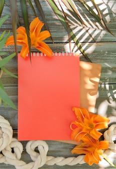 Notebook mock-up met leliebloemen en palmschaduwen