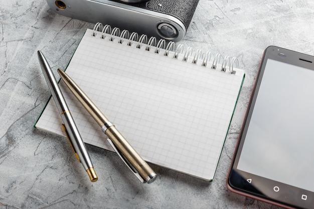 Notebook mock-up voor illustraties met filmcamera en smartphone. bovenaanzicht.