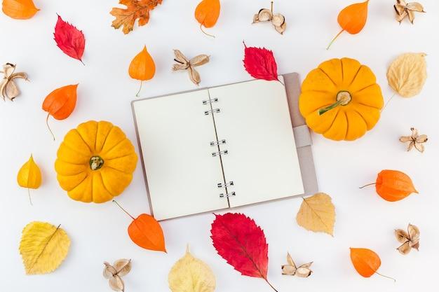 Notebook mockup pompoenen gedroogde bloemen en bladeren