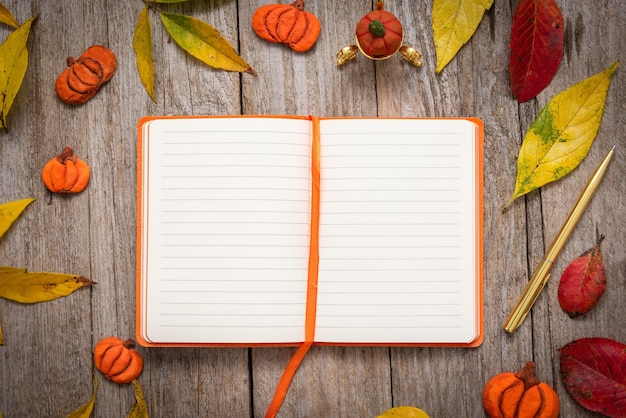 Notebook omgeven door pompoenen en herfstbladeren