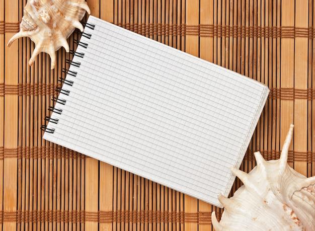 Notebook op de achtergrond van matten en schelpen