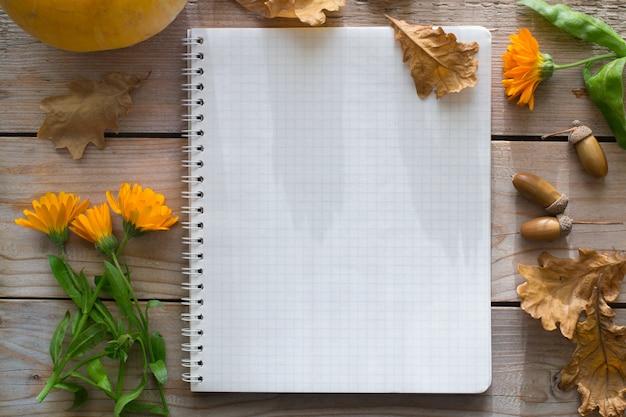 Notebook op houten herfst tafel met pompoen, bloemen droge bladeren