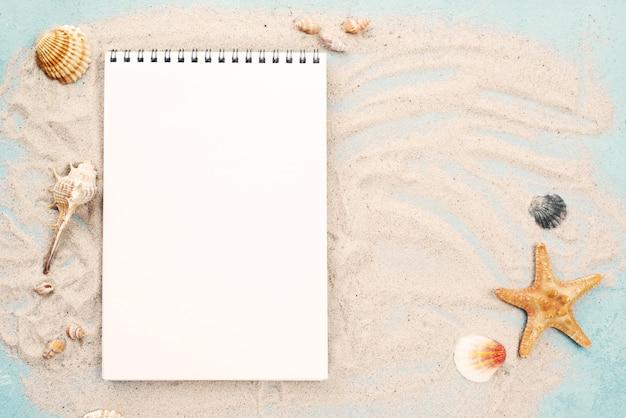 Notebook op zand met schelpen