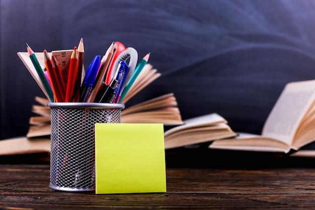 Notebook, open boeken en staan voor pennen op een donkere houten tafel op de achtergrond van schoolbord