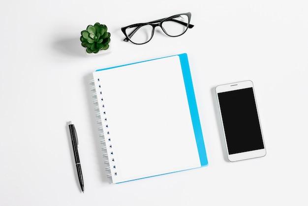 Notebook, pen, bril liggen op een witte achtergrond