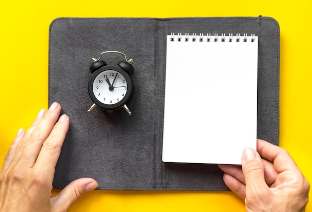 Notebook pen kleine wekker gele achtergrond met kopie ruimte