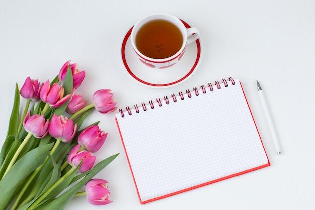 Notebook, pen, kopje thee en een boeket roze tulpen