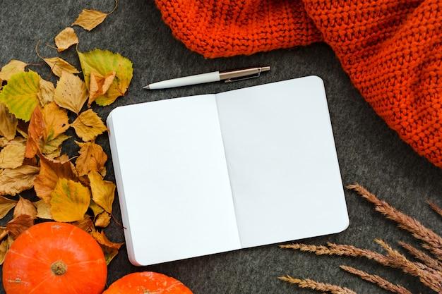 Notebook, pen, pompoenen, gebreide deken en gevallen bladeren