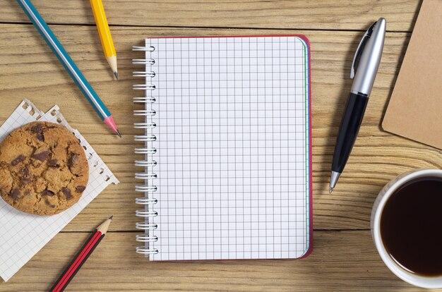 Notebook, pen, potloden en koffie met koekjes op tafel, bovenaanzicht