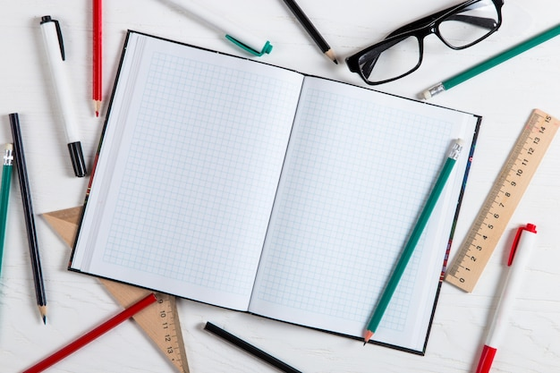 Notebook, potloden, linialen, glazen, markeringen op de witte tafel, kopie ruimte.