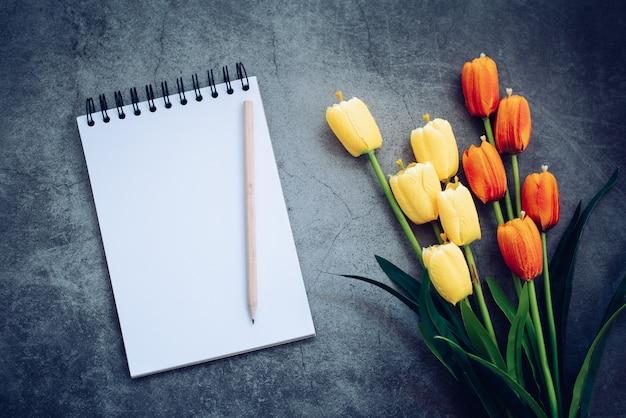 Notebook, potlood en bloem op zwart
