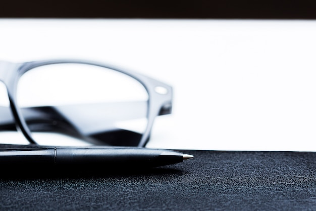 Notebook, potlood en een bril
