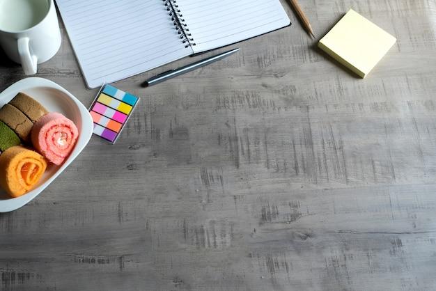 Notebook, smartphone, jambroodje, kopje melk, pen op houten, papieren notitie zakelijk, onderwijsconcept en ontwerp