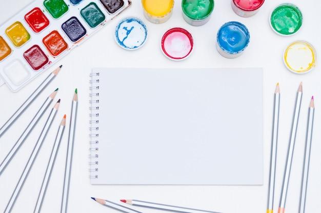 Notebook, verf en potloden op witte achtergrond
