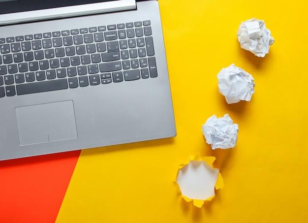 Notebook, verfrommeld papier ballen, op een gele tafel met een gescheurd gat