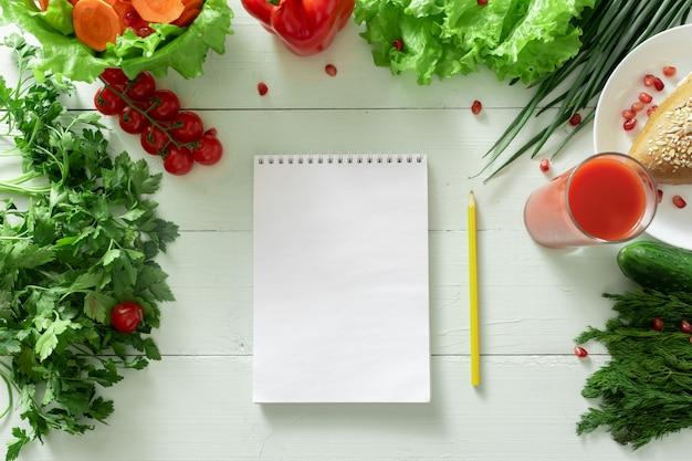Notebook voor het bijhouden van een dagboek van gewichtsverlies op de achtergrond van groenten. een individueel dieet opstellen.