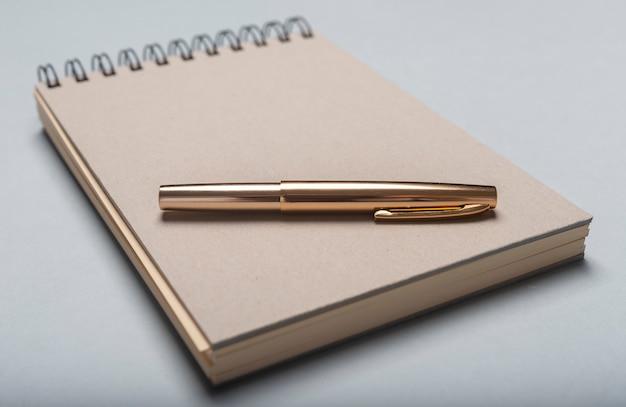 Notebookor blocnote en gouden pen op bureau.