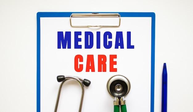Notebookpagina met tekst medische zorg op een tafel met een stethoscoop en een pen