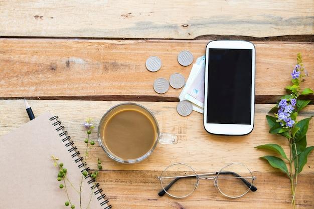 Notebookplanner, contant geld, munten, mobiele telefoon voor zakelijk werk
