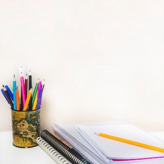 Notebooks in de buurt van beker met potloden