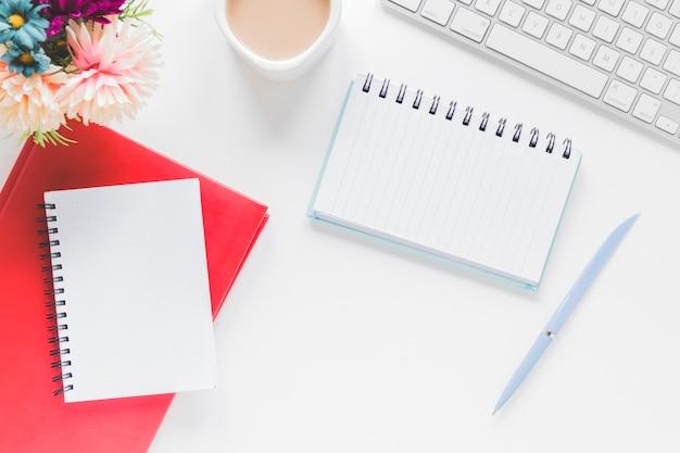 Notebooks in de buurt van koffiekopje en toetsenbord op tafel
