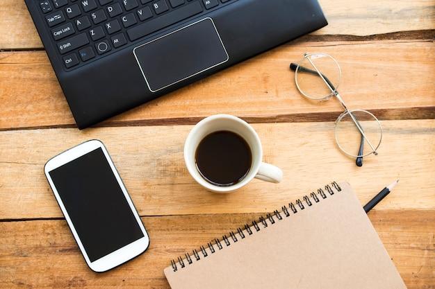 Notebookschaafmachine, mobiele telefoon, computer voor zakelijk werk met hete koffie