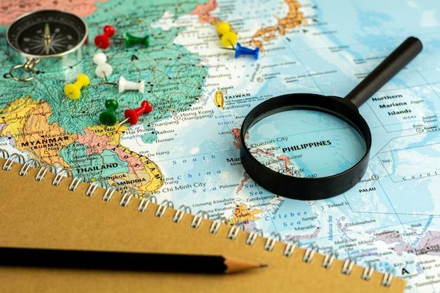 Noteer apparaat en vergrootglas selectief op de kaart van filipijnen. - economisch en reisconcept.