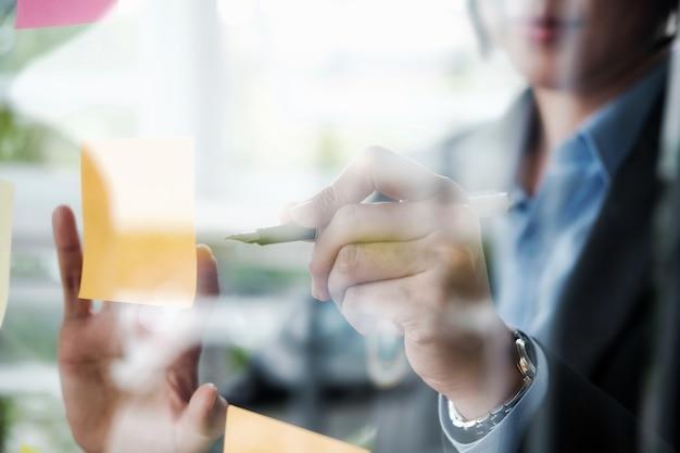 Noteer de papierherinneringsschema. zakenmensen die elkaar ontmoeten en gebruiken, posten notities om idee te delen. bespreking - zaken, teamwork, brainstorming concept.