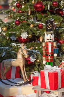 Notekraker en houten paard bij kerstmismarkt in de winter moskou, rusland. adventdecoratie en dennenboom met ambachten geschenken op de bazaar. kerstdecoratie op stadsstraat