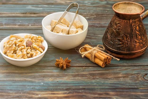 Noten in de kom, koffiepot, kaneel, anijs, suiker op houten achtergrond